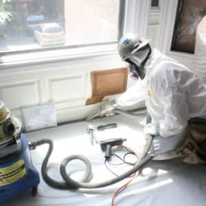 contractor removing lead paint from window and wall