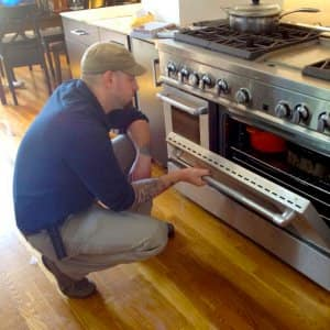 appliance repairman looking into an oven
