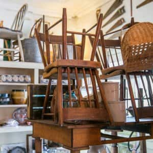 some wooden antique chairs stacked on a table