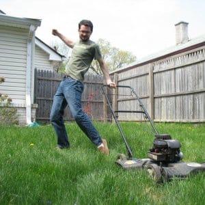 A man starting a push lawnmower