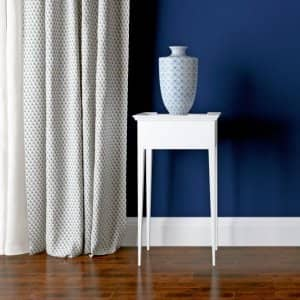 Blue wall, white baseboard in room setting