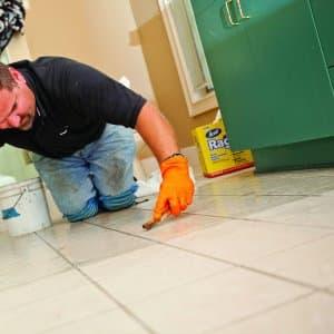 Man regrouting bathroom tile