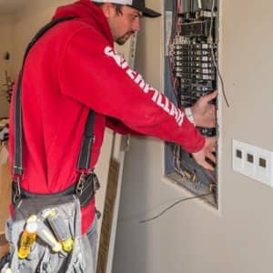 Jordan Giles, an electrician apprentice for Northwest Electric and Solar in Seattle, works to install wiring in a customer's home. (Photo by Mike Penney)