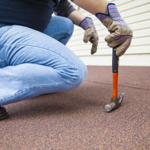 home improvement contractor on roof with hammer