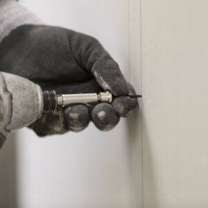 A contractor drills into a wall