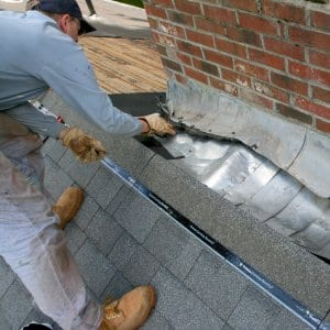 roofing contractor fixing damaged chimney flashing