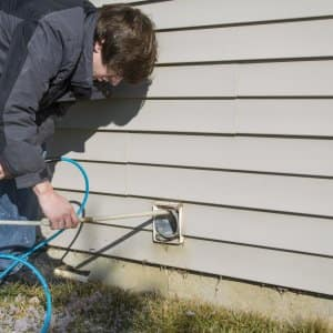 technician performing a dryer vent cleaning at a home