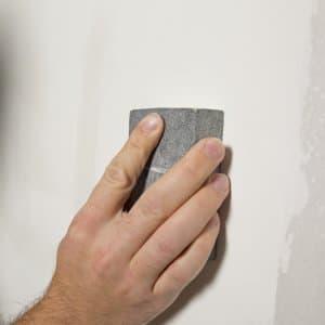 a hand sanding drywall