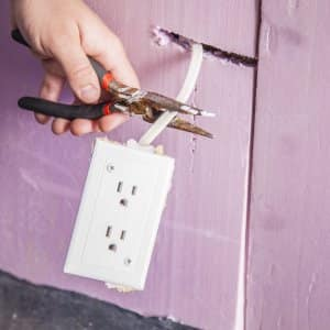 homeowner uses pliers to handle wire and electrical outlet