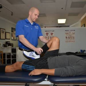 physical therapist assisting man's exercise (Photo by Photo by Dennis Gregg)