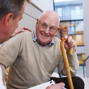 Senior man sits has a friendly conversation with a doctor
