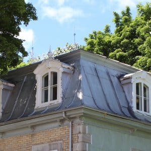 lightning rods atop old home with metal roof