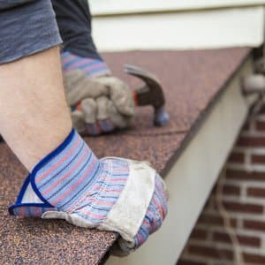 remodeling contractor holds hammer on roof
