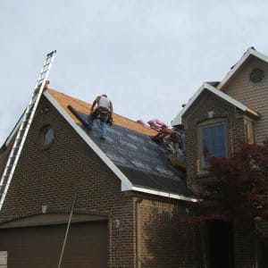 Roofers installing new asphalt shingle roof on home