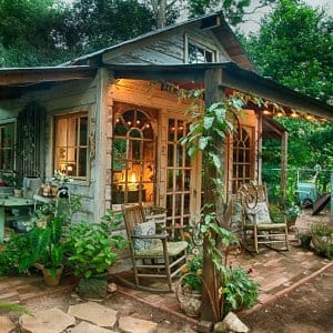 elaborate rustic she-shed with windows, landscaping, roof and lighting