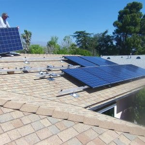 A man installing solar panels on a roof