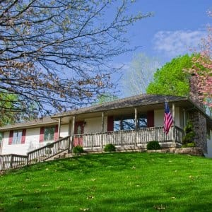 one-story home on a hill with green lawn