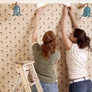 two women removing wallpaper