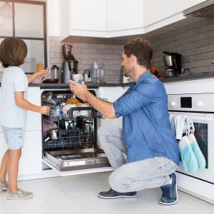 Father and son loading the dishwasher together (Photo by Pikselstock - stock.adobe.com)