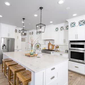 Modern farmhouse kitchen with white marble counters and cabinets (Photo by LUGOSTOCK - stock.adobe.com)