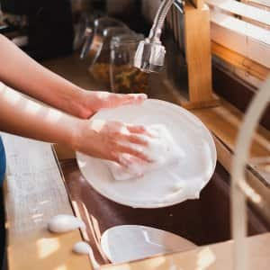 Person using dish soap and sponge to wash a plate (Photo by Nattakorn - stock.adobe.com)