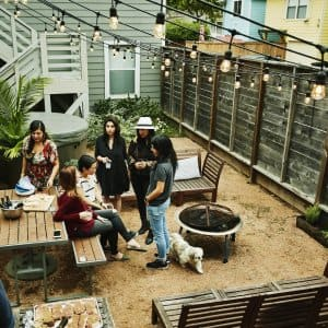 A group of friends hanging out in a backyard at a picnic table surrounded by a dark wooden privacy fence (Photo by Thomas Barwick / DigitalVision via Getty Images)