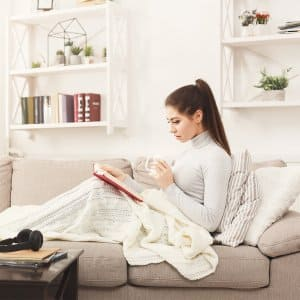 Woman covered up with blanket comfortably on the couch (Photo by Prostock - studio - stock.adobe.com)