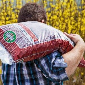 A man carrying a bag of mulch over his shoulder