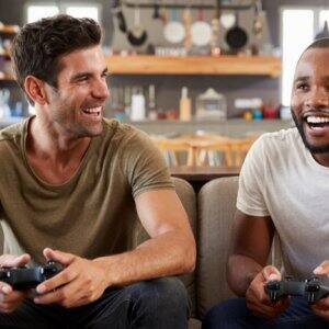 Two friends playing video games in basement (Photo by Monkey Business Images/Shutterstock.com)