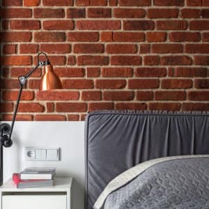 electrical outlet above bedside table in bedroom with brick wall and gray accents (Photo by brizmaker - stock.adobe.com)