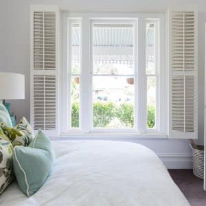Bedroom with shutters at window (Photo by Jodie Johnson - stock.adobe.com)