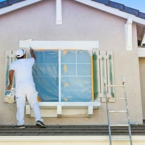 House painter painting the trim and shutters of home (Photo by Feverpitched / iStock / Getty Images Plus via Getty Images)