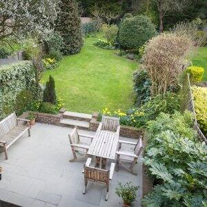 overhead view of concrete patio with lawn furniture next to lush garden flowers and plants and grassy yard (Photo by  PaulMaguire/iStock/Getty Images Plus via Getty Images)