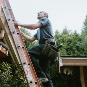 A contractor on a ladder checking a house's roof (Photo by RyanJLane/E+ via Getty Images)