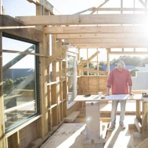 contractor stands at work table in a new house being built (Photo by  Alistair Berg/DigitalVision via Getty Images)