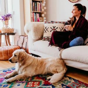 Cozy woman with dog on couch in a boho living room (Photo by Eva Blanco / iStock / Getty Images Plus via Getty Images)