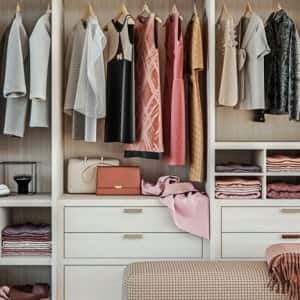 Custom closet with hanging clothes and small bench cushion