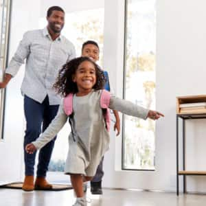 father, daughter and son arriving home through front door (Photo by Monkey Business Images/Shutterstock.com)