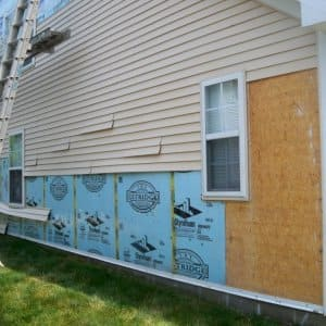 a house with some siding gone because of a storm
