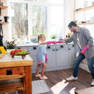 daughter and father fist bump with pink gloves and smile as they prepare to clean the kitchen (Photo by zinkevych - stock.adobe.com.)