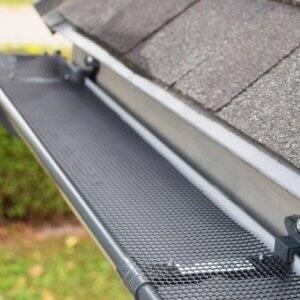 Gutter guard on roof gutters (Photo by ingae / Shutterstock.com)