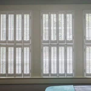 Three large windows with estate shutters in a bedroom (Photo by ucpage/iStock / Getty Images Plus via Getty Images)