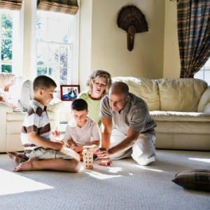 Family laying on the carpet and playing a game (Photo by Gravity Images/The Image Bank via Getty Images)