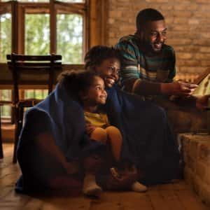 woman, man, and child in cozy blankets huddled next to furnace in low light and smiling (Photo by  BraunS/E+ via Getty Images)