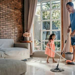Father and daughter mopping living room floor (Photo by Odua Images - stock. adobe.com)
