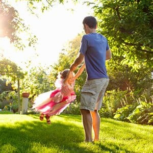 Fathers swings daughter under trees (Photo by Inti St. Clair / Brand X Pictures via Getty Images)