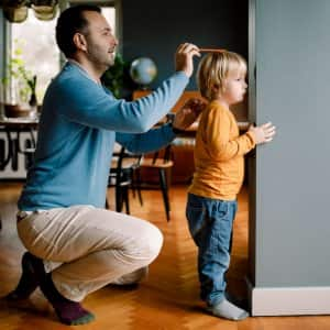 A father measuring daughter's heigh against house wall (Photo by Maskot/Maskot via Getty Images)