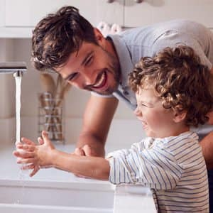 Father helps son wash his hands (Photo by By Monkey Business - stock.adobe.com)