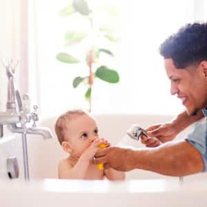 Father giving son a bath (Photo by Halfpoint / Shutterstock.com)