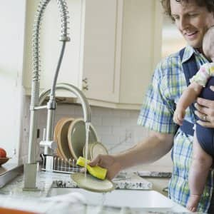 Father washing dishes while carrying baby girl (Photo by Sidekick - stock.adobe.com)